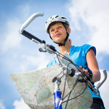 Female cyclist, reading a map, finding her wayの写真素材 [FYI00754023]