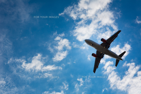 Dark silhouette of an airplane flying over the blue skiesの写真素材 [FYI00754028]