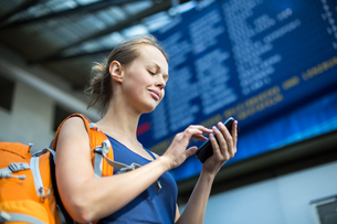 Pretty, young woman in a trainstation, waiting for her train, searching for a connection on her smart phone(color toned image)の写真素材 [FYI00754034]