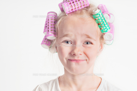 Portrait of emotional cute little girl with curlerの写真素材 [FYI00754446]