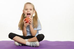 Cheerful girl athlete eating appleの写真素材 [FYI00754622]