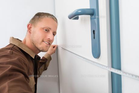 Carpenter Taking Measurement Of Doorの写真素材 [FYI00754923]