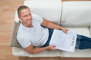 Man On Sofa With Newspaperの写真素材 [FYI00754944]