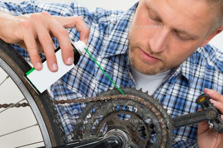 Man Oiling Bicycle Chainの素材 [FYI00754957]