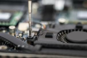 Person Hands Repairing Laptop Motherboardの素材 [FYI00754963]