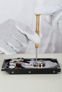 Person Repairing Harddisk Using Screwdriverの写真素材 [FYI00754975]