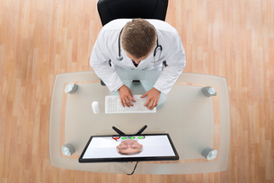 Doctor Videochatting With Senior Colleague On Computerの写真素材 [FYI00754981]