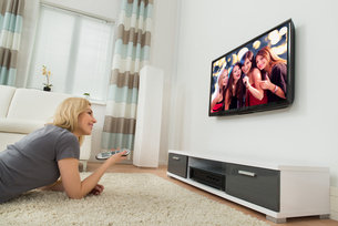 Happy Woman Watching Television At Homeの写真素材 [FYI00755010]
