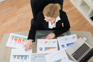 Businesswoman Analyzing Financial Graphsの写真素材 [FYI00755016]