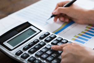 Businesswoman Analyzing Financial Report With Calculatorの写真素材 [FYI00755028]