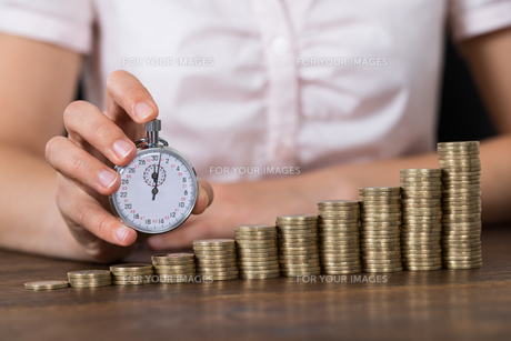 Businessperson With Stopwatch And Stack Of Coinsの写真素材 [FYI00755031]