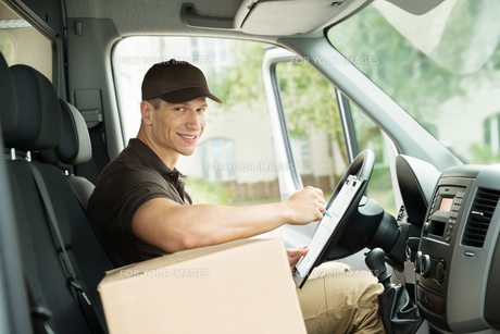 Happy Delivery Man Checking Listの写真素材 [FYI00755061]