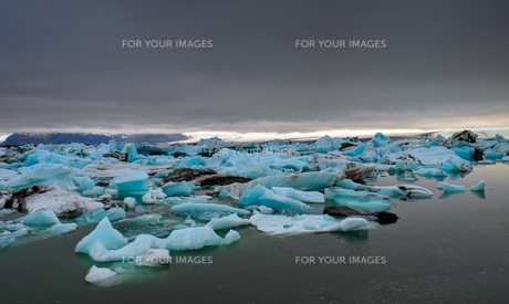 dark clouds over a glacial lagoon in icelandの写真素材 [FYI00755848]