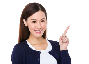 Asian young woman with finger point upwards for selling somethingの素材 [FYI00757313]