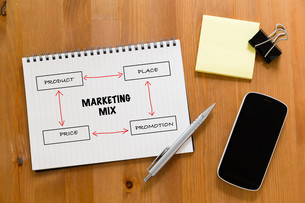 Working desk with mobile phone and handbook showing marketing mix conceptの写真素材 [FYI00757541]