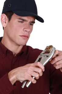 Plumber holding wrench and pipeの写真素材 [FYI00757545]