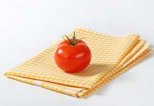 Checked tea towel and red tomatoの写真素材 [FYI00757955]