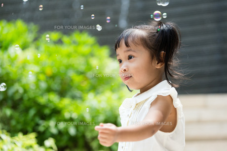 Asian baby girl play bubble blower at outdoorの素材 [FYI00758092]