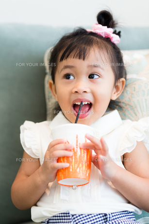 Excited girl drinking at homeの写真素材 [FYI00758106]