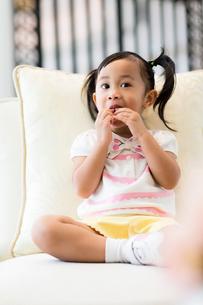 Little girl having snack and sitting on sofaの写真素材 [FYI00758126]