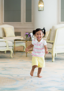 Excited girl running at homeの写真素材 [FYI00758132]