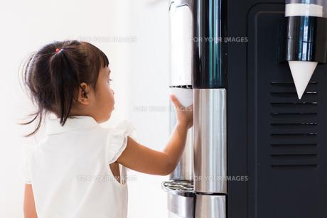Baby girl using the water machineの素材 [FYI00758139]