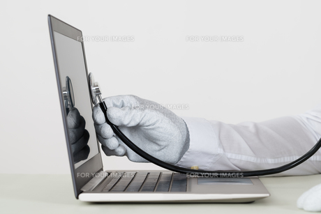 Person Hands Checking Laptop With Stethoscopeの写真素材 [FYI00758703]