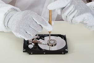 Person Repairing Harddisk Using Screwdriverの写真素材 [FYI00758714]