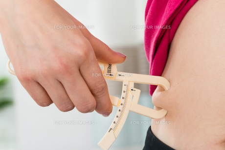 Female Hands Measuring Fat Bellyの写真素材 [FYI00758748]