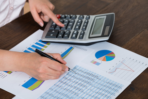 Businesswoman Analyzing Financial Report With Calculatorの写真素材 [FYI00758784]