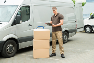Delivery Man Writing On Clipboardの写真素材 [FYI00758788]