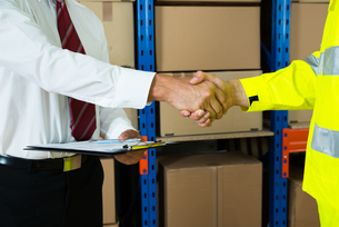 Close-up Of Businessman And Warehouse Worker Shaking Handsの写真素材 [FYI00758828]