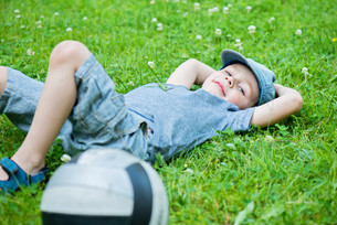 Little caucasian boy resting on grassの素材 [FYI00758842]