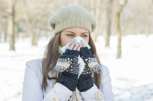 Young Woman in Winter Clothing Blowing Noseの素材 [FYI00759050]