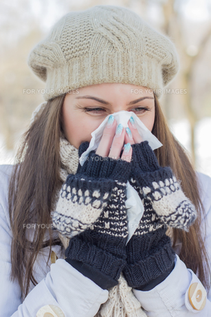 Young Woman in Winter Clothing Blowing Noseの素材 [FYI00759059]