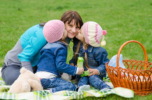 Two daughters kissing mother while on a picnicの写真素材 [FYI00759856]