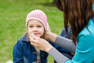 Mother wipes his mouth with a napkin girl on picnicの写真素材 [FYI00759857]