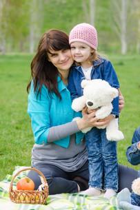 Mother hugs daughter at a picnicの写真素材 [FYI00759859]