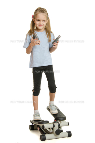 Six year old girl on a step simulator with expander in the hands ofの写真素材 [FYI00759868]