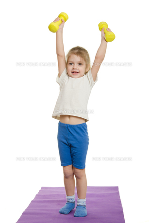 Four-year-girl lifted dumbbells over aの写真素材 [FYI00759874]