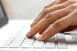 fingers typing on white laptop computer keyboardの写真素材 [FYI00760223]