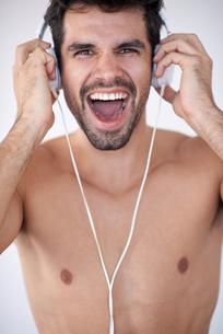 handsome young man listening music on headphonesの写真素材 [FYI00760225]