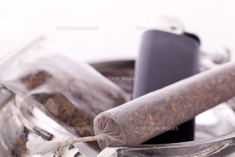 cannabis marijuana with water pfeifer and joint with grass and ashtrayの写真素材 [FYI00760399]