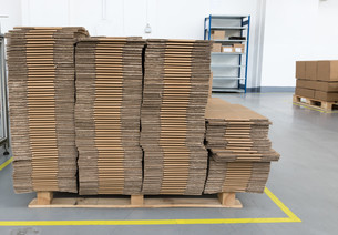 Front view of folded cardboard boxes in assembly hallの写真素材 [FYI00760407]