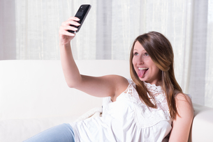 attractive young girl shooting selfie with tongue outの写真素材 [FYI00760502]