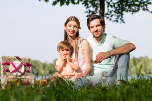 Family having picnic at lake sitting on meadowの写真素材 [FYI00760973]