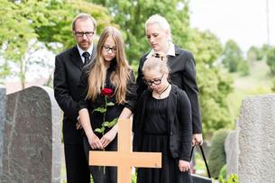 Familie steht in Trauer an Grab auf Friedhofの素材 [FYI00761014]