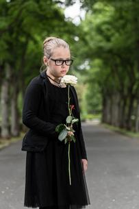 M?dchen mit wei?er Rose trauert auf Friedhofの素材 [FYI00761021]