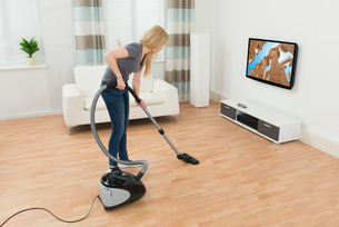Woman Cleaning Floor With Vacuum Cleanerの写真素材 [FYI00761057]