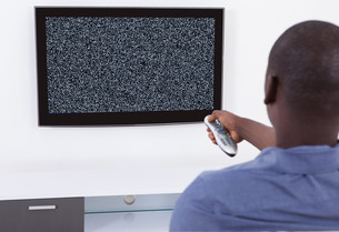 Man With Remote Watching Televisionの写真素材 [FYI00761059]